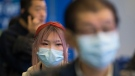 Passengers wear masks as they arrive at the international arrivals area at the Vancouver International Airport in Richmond, B.C., Thursday, Jan. 23, 2020. (THE CANADIAN PRESS / Jonathan Hayward)