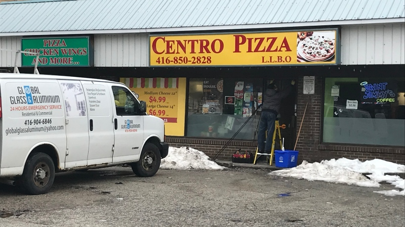 Crews work on repairing a shop after shots were fired in the area of Markham and Kingston Roads on Jan. 25. (Nick Dixon/CTV News Toronto)