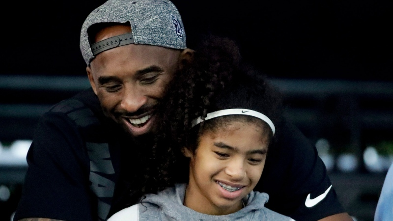 FILE - In this July 26, 2018 file photo former Los Angeles Laker Kobe Bryant and his daughter Gianna watch during the U.S. national championships swimming meet in Irvine, Calif. (AP Photo/Chris Carlson)