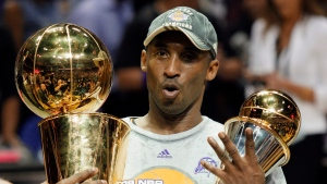 In this June 14, 2009 file photo Los Angeles Lakers' Kobe Bryant holds the Larry O'Brien championship trophy and finals MVP trophy after the Lakers defeated the Orlando Magic 99-86 in Game 5 of the NBA basketball finals in Orlando, Fla. (AP Photo/David J. Phillip)