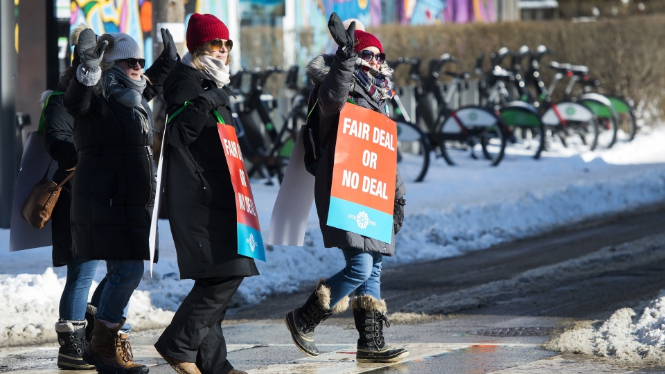 Teachers of the Elementary Teachers' Federation of Ontario wave to honking cars as they participate in a full withdrawal of services strike in Toronto on January 20, 2020. THE CANADIAN PRESS/Nathan Denette