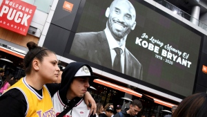 Fans mourn the loss of Kobe Bryant in front of La Live across from Staples Center, home of the Los Angeles Lakers in Los Angeles on Sunday, Jan, 26, 2020. Bryant, the 18-time NBA All-Star who won five championships and became one of the greatest basketball players of his generation during a 20-year career with the Lakers, died in a helicopter crash Sunday. (Keith Birmingham/The Orange County Register via AP)