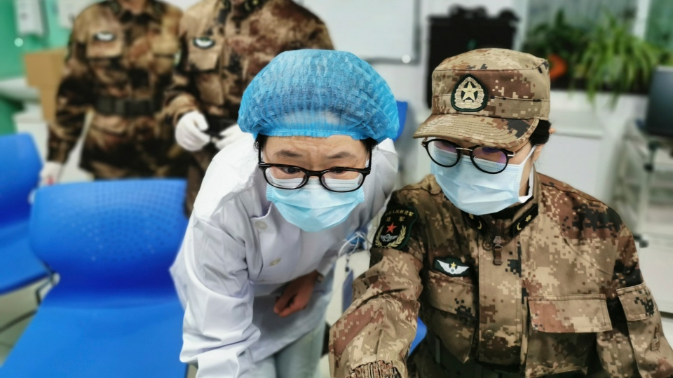 In this Jan. 26, 2020, photo released by Xinhua News Agency, a member of a military medical team takes over the work from a medical worker at Wuhan Jinyintan Hospital in Wuhan, central China's Hubei province. C (Li Yun/Xinhua via AP)