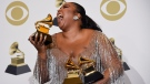 Lizzo poses in the press room with the awards for best pop solo performance, best urban contemporary album and best traditional R&B performance at the 62nd annual Grammy Awards at the Staples Center on Sunday, Jan. 26, 2020, in Los Angeles. (AP Photo/Chris Pizzello)