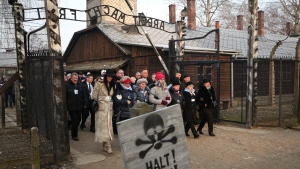 Poland's President Andrzej Duda walks along with survivors through the gates of the Auschwitz Nazi concentration camp to attend the 75th anniversary of its liberation in Oswiecim, Poland, Monday, Jan. 27, 2020. (AP Photo/Czarek Sokolowski)