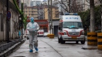 In this Sunday, Jan. 26, 2020 photo, an ambulance crew member in protective gear carries a box of medical supplies in Wuhan in central China's Hubei Province. (Chinatopix via AP)