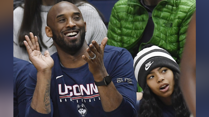 In this March 2, 2019 photo, Kobe Bryant and his daughter Gianna watch the first half of an NCAA college basketball game between Connecticut and Houston in Storrs, Conn. Bryant, the 18-time NBA All-Star who won five championships and became one of the greatest basketball players of his generation during a 20-year career with the Los Angeles Lakers, died in a helicopter crash Sunday, Jan. 26, 2020. Gianna also died in the crash. (AP Photo/Jessica Hill)
