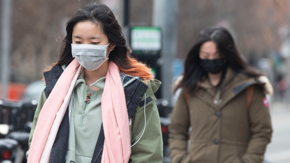 Pedestrians wear face masks as they walk in downtown Toronto, on Monday January 27, 2020, as officials announce that Canada has its second presumptive positive case of the new coronavirus. THE CANADIAN PRESS/Chris Young