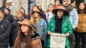 Ta'Kaiya, front, and Sii-am Hamilton, holding a sign, are seen standing with Indigenous youth demonstrating support for the Wet'suwet'en hereditary chiefs in northwest B.C. opposing the LNG pipeline project, in front of the B.C. legislature in Victoria on Friday, Jan. 24, 2020. (Dirk Meissner / The Canadian Press)