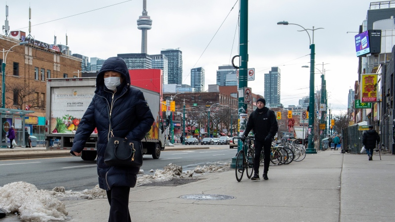 A pedestrian wears a protective mask in Toronto on Monday, January 27, 2020. Canada's first presumptive case of the novel coronavirus has been officially confirmed, Ontario health officials said Monday as they announced that the patient's wife has also contracted the illness. THE CANADIAN PRESS/Frank Gunn