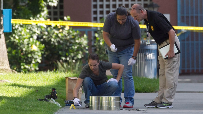 In this July 6, 2016, file photo, San Diego's Metro Arson Strike Team and SDPD homicide team gather evidence from the sidewalk and grassy area where a homeless person was attacked in downtown San Diego. Jon David Guerrero pleased guilty on Monday to four counts of murder in a string of deadly attacks on homeless men. (John Gibbins/U-T San Diego via AP, File)