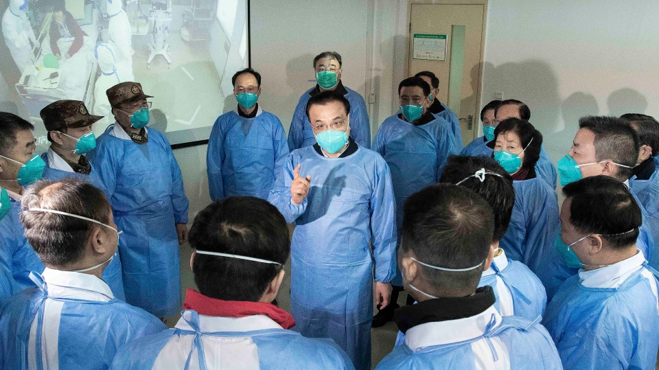 In this photo released by China's Xinhua News Agency, Chinese Premier Li Keqiang, centre, speaks with medical workers at Wuhan Jinyintan Hospital in Wuhan in central China's Hubei province, Monday, Jan. 27, 2020.  (Li Tao/Xinhua via AP)