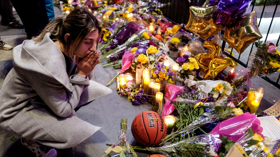 A fan pays her respects at a memorial for Kobe Bryant near Staples Center, Monday, Jan. 27, 2020, in Los Angeles. (AP Photo/Ringo H.W. Chiu)
