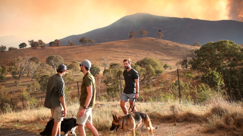 Wildfire smoke billows behind a mountain range on Tuesday, jan. 28, 2020, close to Canberra's southern outskirts. (AP Photo/Rod McGuirk)