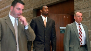 In this Wednesday, March 24, 2004, file photo, Los Angeles Lakers' Kobe Bryant, center, walks out of a holding area as he prepares to leave for a lunch break from proceedings in his sexual assault case as members of his security team accompany him, in Eagle, Colo. (AP Photo/Ed Andrieski, File)