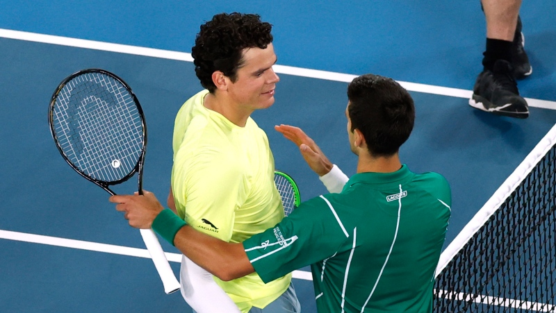 Serbia's Novak Djokovic, right, is congratulated by Canada's Milos Raonic after winning their quarterfinal match at the Australian Open tennis championship in Melbourne, Australia, Tuesday, Jan. 28, 2020. (AP Photo/Andy Wong)