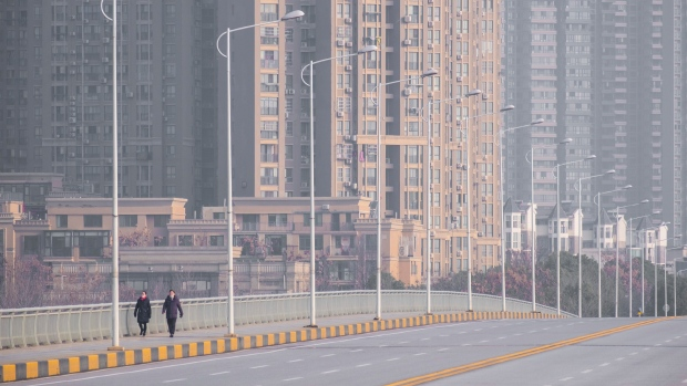 People wearing face masks walk down a deserted street in Wuhan in central China's Hubei Province, Tuesday, Jan. 28, 2020. (AP Photo/Arek Rataj)