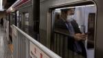 A commuter wearing a mask waits for a train to depart at Shinjuku Station in Tokyo, Monday, Jan. 27, 2020. (AP Photo/Jae C. Hong)