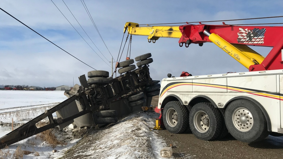 A truck being lifted out of a snowy ditch