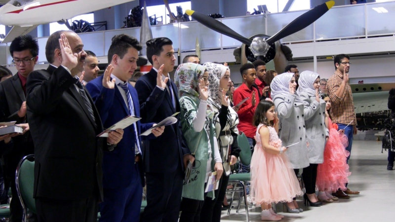 Members of the Altamky family take an oath during a Canadian citizenship ceremony at the Hangar Museum in Calgary