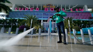 Moisr Altidor pressure washes the sidewalk outside of Hard Rock Stadium Tuesday, Jan. 28, 2020, in Miami Gardens, Fla. in preparation for the NFL Super Bowl 54 football game between the San Francisco 49ers and the Kansas City Chiefs. (AP Photo/Chris Carlson)