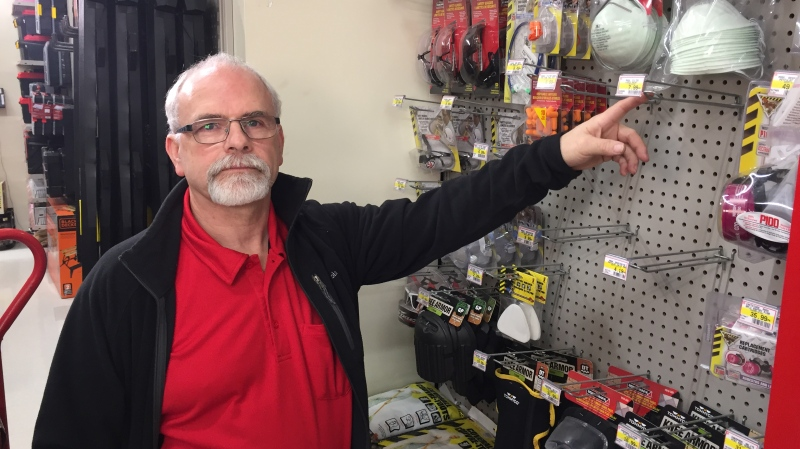 Rob Borshell points to empty racks for masks at Tuckey Home Hardware in London, Ont. on Tuesday, Jan. 28, 2020. (Bryan Bicknell / CTV London)