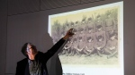 Historian Martin Cueppers points at a man, presumably former security guard John Demjanjuk, at the Nazi death camp Sobibor during a news conference of newly discovered photos from the Sobibor camp in Berlin, Germany, Tuesday, Jan. 28, 2020. (AP Photo/Markus Schreiber)