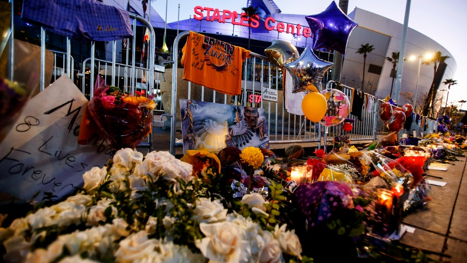 Flowers and messages are placed at a memorial for Kobe Bryant in front of Staples Center, Tuesday, Jan. 28, 2020, in Los Angeles. (AP Photo/Ringo H.W. Chiu)