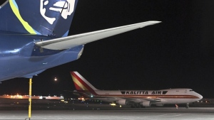 An airplane, background, carrying U.S. citizens being evacuated from Wuhan, China, makes a refueling stop at the north terminal at Ted Stevens Anchorage International Airport in Anchorage, Alaska Tuesday evening, Jan. 28, 2020. (Bill Roth/Anchorage Daily News via AP)
