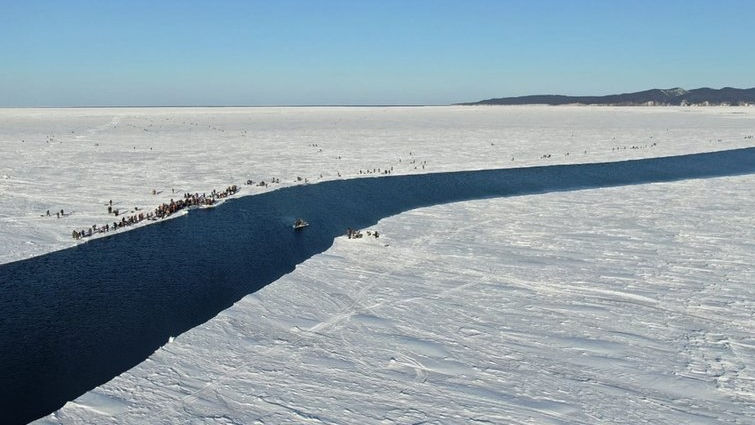 In this Tuesday, Jan. 28, 2020 photo a group of fishermen use a smaller piece of ice as a raft trying to row to the coast, as the ice floe with stranded fishermen on them slowly drifted further away from the land at the Mordvinov's Bay in eastern Siberia, Russia. (Russia Emergency Situations Ministry press service via AP)