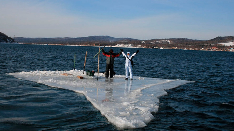 In this Jan. 28, 2020 photo released by the Russia Emergency Situations Ministry press service, showing two fishermen using a smaller piece of ice as a raft and trying to row to the land, as the ice floe with stranded fishermen on them slowly drifted further away from land at Mordvinov's Bay in eastern Siberia, Russia. (Russia Emergency Situations Ministry press service via AP)