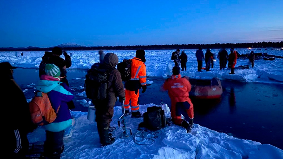 In this Tuesday, Jan. 28, 2020 photo released by the Russia Emergency Situations Ministry press service, showing rescuers in foreground as they help a group of fishermen to get to the land, using a small boat at the Mordvinov's Bay, the island of Sakhalin in eastern Siberia, Russia. Russia's emergency services have rescued 536 ice fishermen after they got stranded on a giant ice floe that broke off the island of Sakhalin in eastern Siberia. (Russia Emergency Situations Ministry press service via AP)