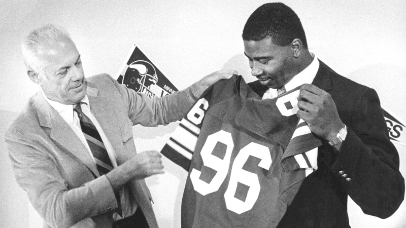 Minnesota Vikings head coach Bud Grant holds up the new jersey to their first-round draft pick Chris Doleman, on May 1, 1985. (Larry Salzman / AP)
