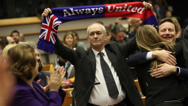 British MEP Richard Corbett holds a banner after a vote on the UK's withdrawal from the EU, the final legislative step in the Brexit proceedings, during the plenary session at the European Parliament in Brussels, Wednesday, Jan. 29, 2020. The U.K. is due to leave the EU on Friday, Jan. 31, 2020, the first nation in the bloc to do so. (AP Photo/Francisco Seco, Pool)