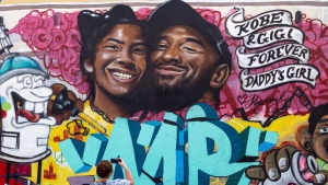 Bryan Esparaza and her daughter Amelia, 4, pause in front of a mural put up of Kobe Bryant and his daughter along Pickford Street in Los Angeles, Monday, Jan. 27, 2020. Bryant, the 18-time NBA All-Star who won five championships and became one of the greatest basketball players of his generation during a 20-year career with the Los Angeles Lakers, died in a helicopter crash Sunday. (David Crane/The Orange County Register via AP)