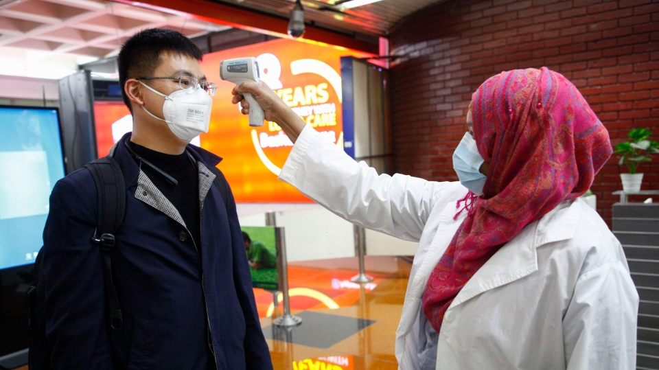A passenger from Beijing is screened as part of measures to prevent coronavirus infection at Hazrat Shahjalal International airport in Dhaka, Bangladesh, Wednesday, Jan.29, 2020. (AP Photo/Al-emrun Garjon)