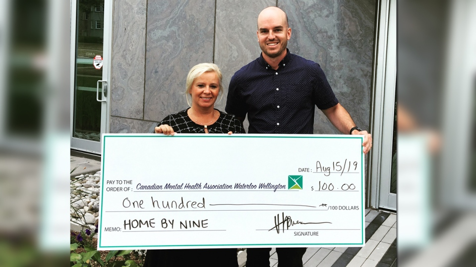 A man and woman holding a giant cheque