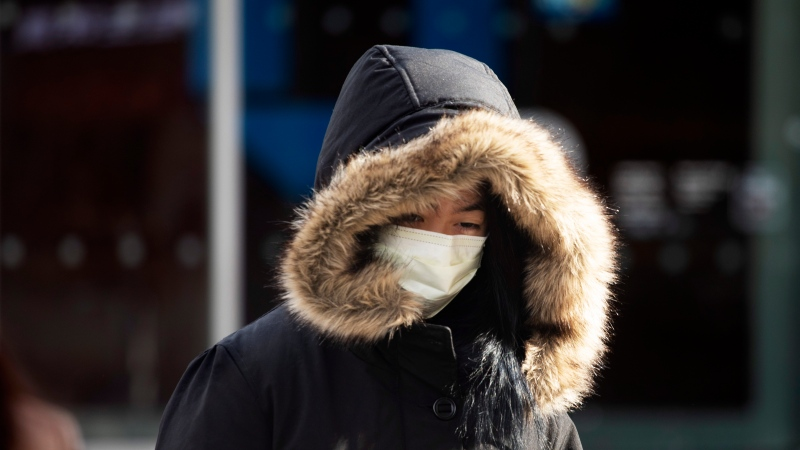 """A woman, who declined to give her name, wears a mask, Thursday, Jan. 30, 2020 in New York. She works in a doctor's office and said she wears the mask """"partly"""" out of concern for the coronavirus. For the first time in the U.S., the new virus from China has spread from one person to another, health officials said Thursday. (AP Photo/Mark Lennihan)"""