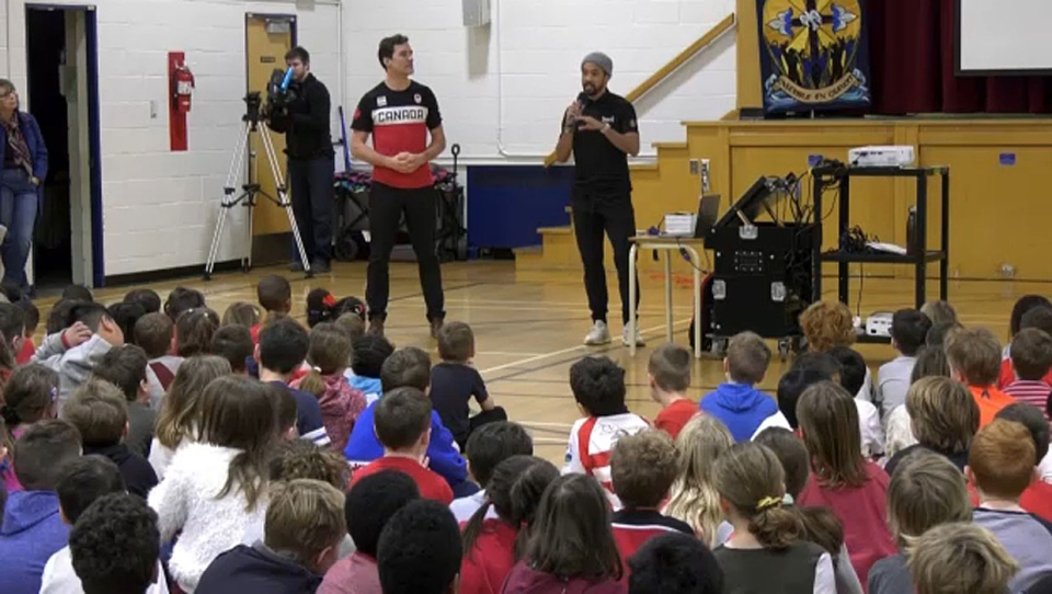 Canadian speed skating Olympians Denny Morrison (right) and Gilmore Junio (left) speak to students of Holy Name School about the importance of teamwork.