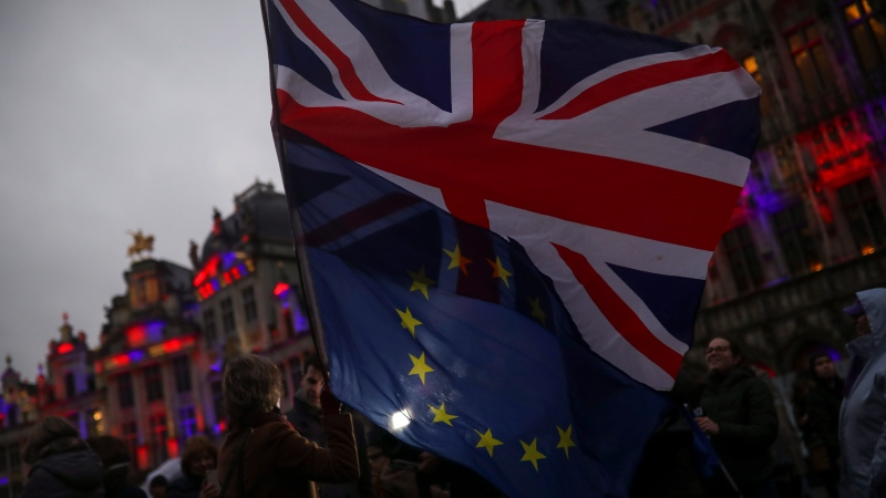 """A woman holds up the Union and the European Union flags during an event called """"Brussels calling"""" to celebrate the friendship between Belgium and Britain at the Grand Place in Brussels, Thursday, Jan. 30, 2020. (AP Photo/Francisco Seco)"""