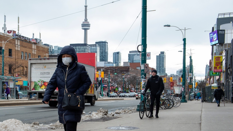 A pedestrian wears a protective mask in Toronto on Monday, January 27, 2020. The World Health Organization declared the outbreak sparked by a new virus in China that has spread to more than a dozen countries as a global emergency Thursday after the number of cases spiked more than tenfold in a week. (THE CANADIAN PRESS/Frank Gunn)