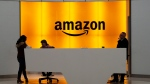 In this Feb. 14, 2019 file photo, people stand in the lobby for Amazon offices in New York. (AP Photo/Mark Lennihan, File)