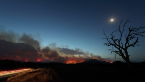 A car's taillights streak past at left as a wildfire threatening property glows at dusk near Clear Range, south of the Australian capital, Canberra, Friday, Jan. 31, 2020. The threat is posed by a blaze on Canberra's southern fringe that has razed more than 21,500 hectares (53,000 acres) since it was sparked by heat from a military helicopter landing light on Monday, the Emergency Services Agency said.(AP Photo/Rick Rycroft)