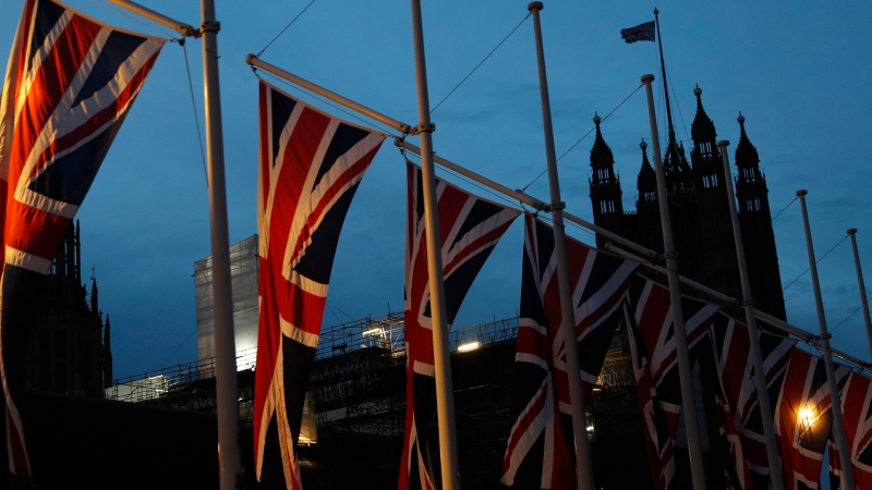 The first light of dawn breaks looking towards the Palace of Westminster with British Union flags flying in London, Saturday, Feb. 1, 2020. (AP Photo/Alastair Grant)