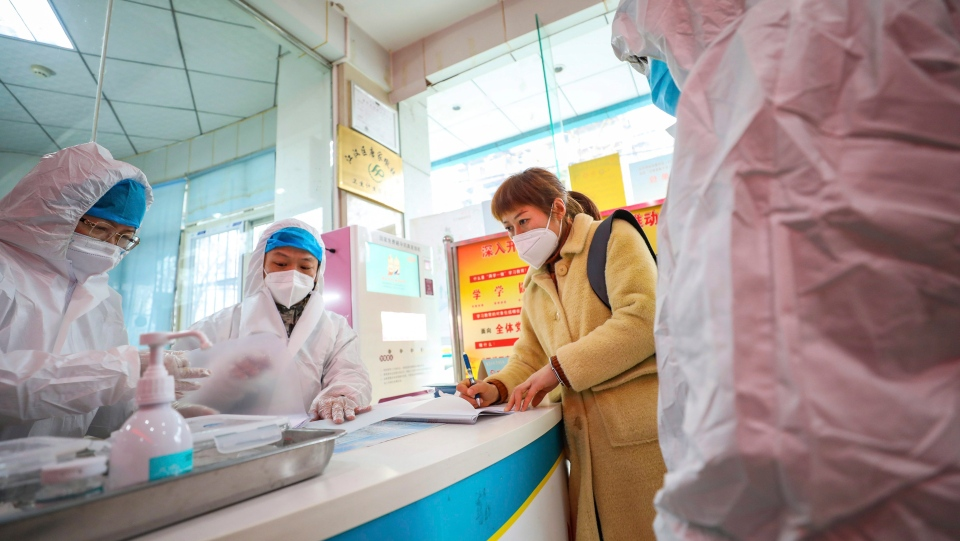Medical workers in protective gear talk with a woman suspected of being ill with a coronavirus at a community health station in Wuhan in central China's Hubei Province, Monday, Jan. 27, 2020. (Chinatopix via AP