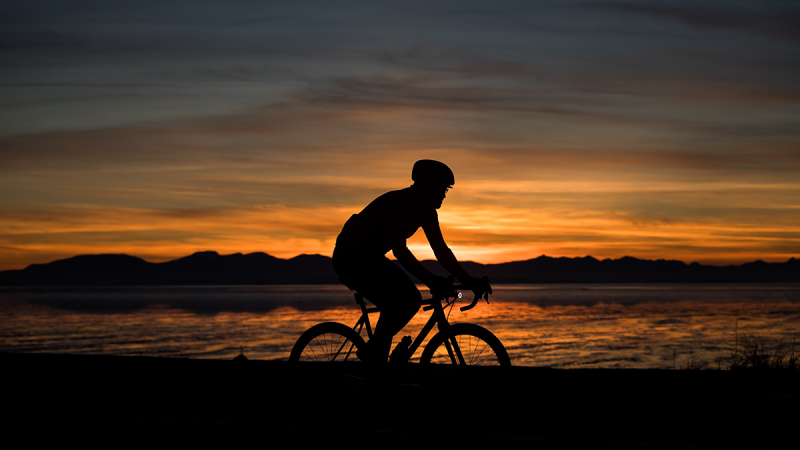 A man is silhouetted while cycling at sunset at Iona Beach Regional Park, in Richmond, B.C., on Tuesday, Jan. 29, 2019. (Darryl Dyck / THE CANADIAN PRESS)