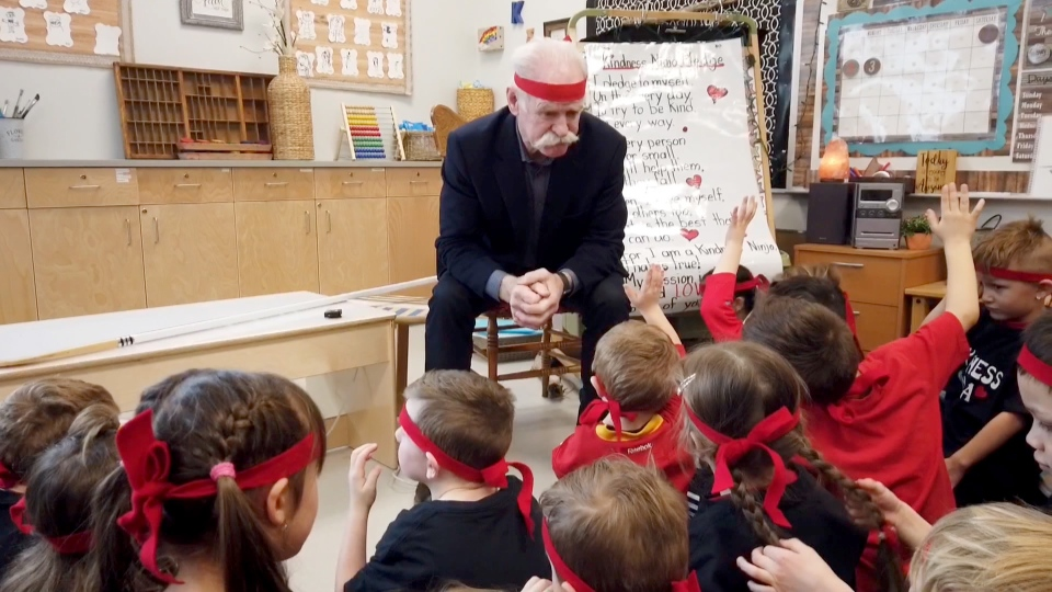 Lanny McDonald sits with kindergarten students at Windsong Heights School in Airdrie after joining them in becoming a Kindness Ninja.