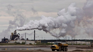 A dump truck works near the Syncrude oil sands extraction facility near the city of Fort McMurray, Alta., on June 1, 2014. The parliamentary budget office says most Canadian households will receive more money back from the federal government's carbon-tax scheme than it will cost them. The assertion is contained in a report published by the PBO this morning, nearly four months after a majority of Canadian voters cast their ballots in favour of parties that favoured a carbon tax. THE CANADIAN PRESS/Jason Franson
