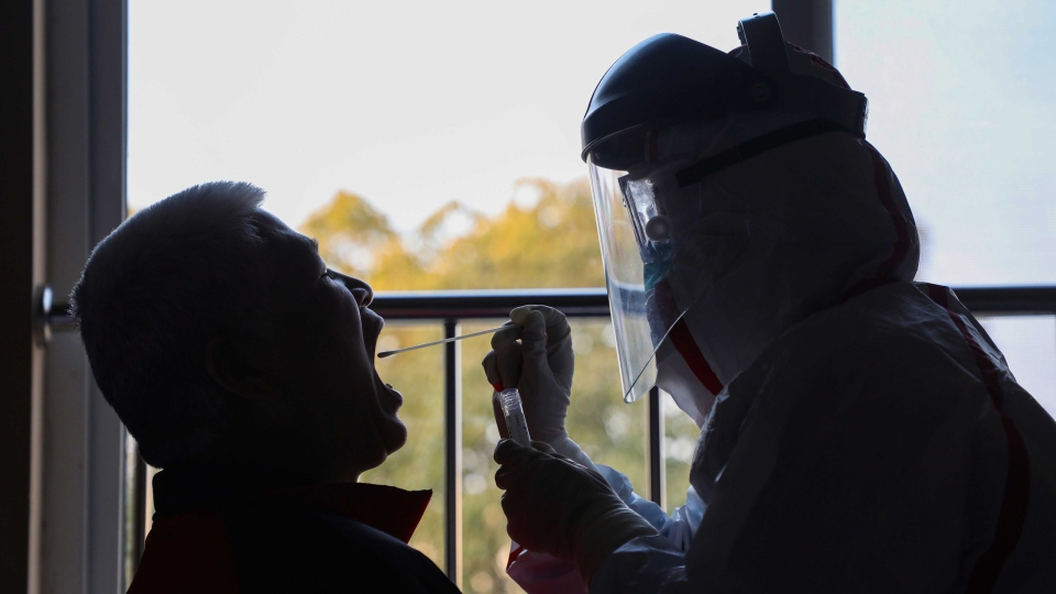 A medical worker in a protective suit collects a sample for nucleic acid tests from a suspected virus patient at a hotel being used to place people in medical isolation in Wuhan in central China's Hubei Province, Tuesday, Feb. 4, 2020. (Chinatopix via AP)