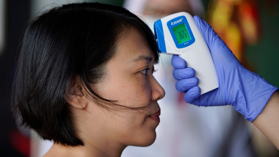 A nurse checks the temperature of a visitor as part of the coronavirus screening procedure at a hospital in Kuala Lumpur, Malaysia, Wednesday, Feb. 5, 2020. (AP Photo/Vincent Thian)